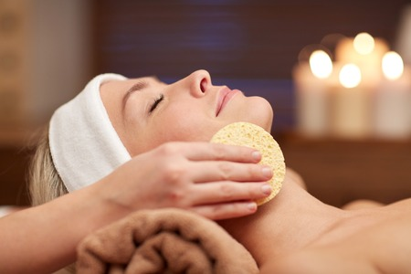 young skin: people, beauty, spa, cosmetology and relaxation concept - close up of beautiful young woman lying with closed eyes having face cleaning by sponge in spa Stock Photo