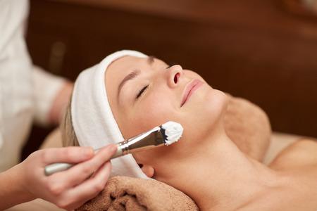 limpieza de cutis: personas, belleza, spa, cosmetología y cuidado de la piel concepto - cerca de la hermosa mujer joven tendido con los ojos cerrados y cosmetóloga que aplican la máscara facial con brocha en el spa