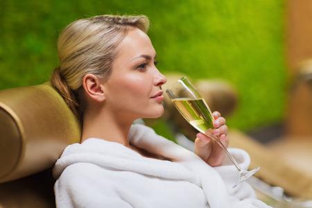 jovenes tomando alcohol: personas, belleza, estilo de vida, las vacaciones y el concepto de relajaci�n - hermosa mujer joven en traje de ba�o blanco acostado en chaise-longue y bebiendo champ�n en el spa