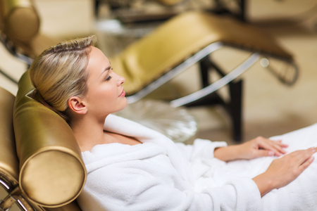bath: people, beauty, healthy lifestyle and relaxation concept - beautiful young woman lying on chaise-longue in bath robe at spa