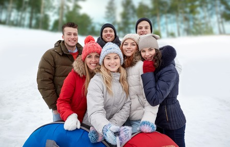 winter woman: winter, leisure, friendship, technology and people concept - group of smiling young men and women with snow tubes taking picture with smartphone selfie stick outdoors