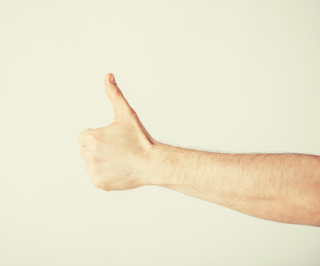 close up of man hand showing thumbs up photo