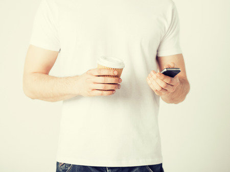 take away: man with smartphone and take away coffee cup