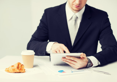 snack time: close up of man with tablet pc and cup of coffee