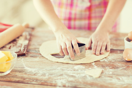 making up: cooking and home concept - close up of female hands making cookies from fresh dough at home