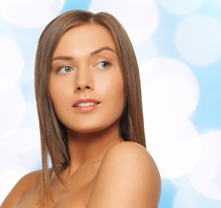 bare shoulders: beauty, people and health concept - beautiful young woman with bare shoulders over blue lights background