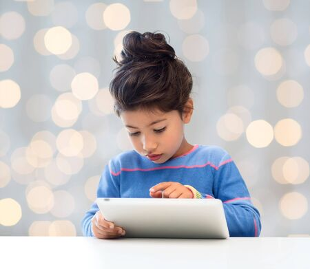 preteen asian: education, technology and children concept - little student girl with tablet pc over holidays lights background