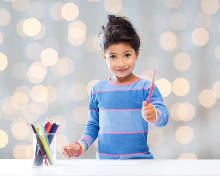 preteen asian: children, creativity and happy people concept - happy little girl drawing with coloring pencils over holidays lights background