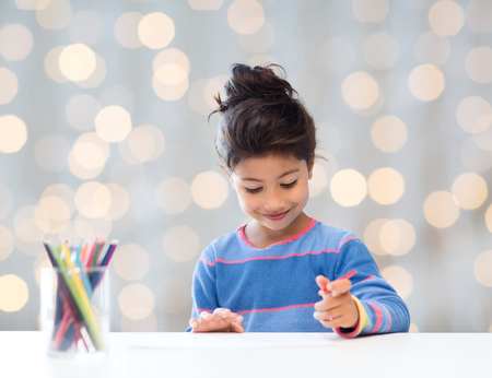 asian art: children, creativity and happy people concept - happy little girl drawing with coloring pencils over holidays lights background