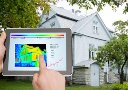 energie: Haus, Wohnung, Menschen und Technologie-Konzept - Nahaufnahme von Menschen die Hände, der Finger zeigt auf Tablet PC Computer und Regelraumtemperatur über Haus Hintergrund