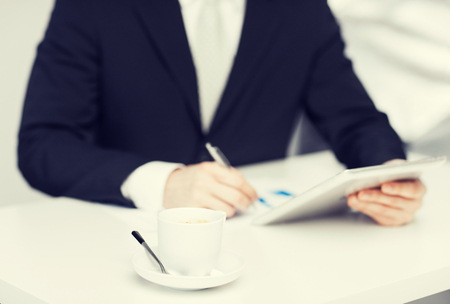 cashflow: man with tablet pc, cup of coffee and graphs Stock Photo