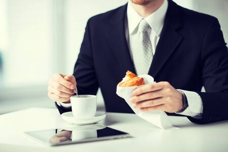 work break: man with tablet pc, cup of coffee and croissant