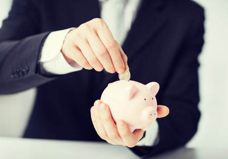 thrifty: picture of man putting coin into small piggy bank Stock Photo