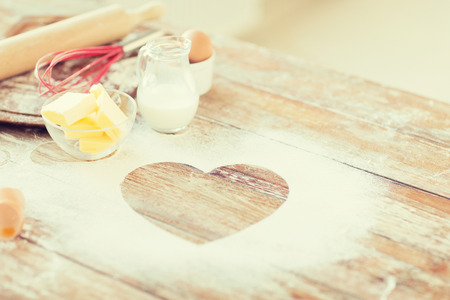 cooking and love concept - close up of heart of flour on wooden table at home 스톡 콘텐츠