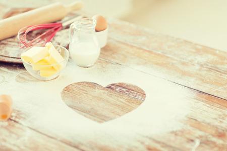 cocinando: la cocina y el concepto de amor - cerca de centro de la harina en la mesa de madera en casa Foto de archivo