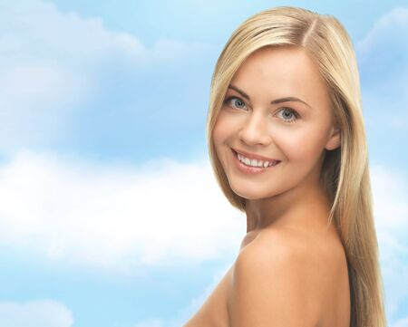 beautiful weather: people, beauty, body and skin care concept - beautiful woman face and hands over blue sky background
