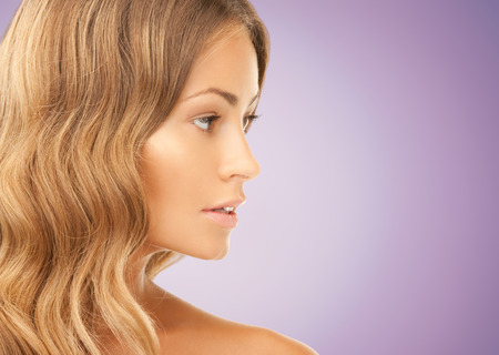 long nose: beauty, people and health concept - beautiful young woman face over violet background Stock Photo