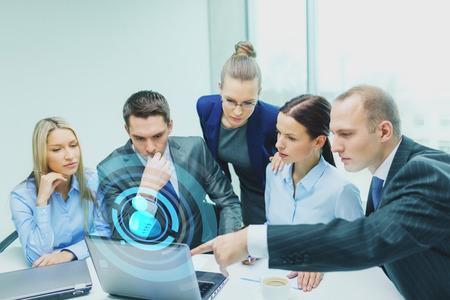 비즈니스, 기술 및 사람들이 개념 - 심각한 비즈니스 팀 랩톱 컴퓨터 및 사용자 아이콘 투영 사무실에서 토론을 데