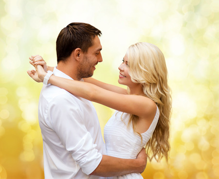 man woman hugging: holidays, people, love and dating concept - happy couple hugging over yellow lights background