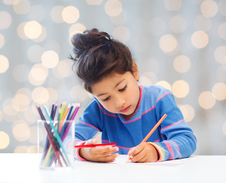 asian art: children, hobby, childhood and happy people concept - little girl drawing over holidays lights background Stock Photo