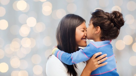 asian child: family, children and happy people concept - happy little girl hugging and kissing her mother over holidays lights background