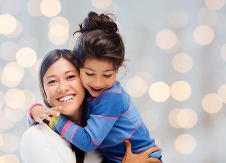 madre: la gente, la felicidad, el amor, la familia y la maternidad concepto - feliz madre e hija abrazos durante las vacaciones luces de fondo
