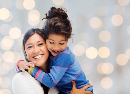 asian child: people, happiness, love, family and motherhood concept - happy mother and daughter hugging over holiday lights background Stock Photo