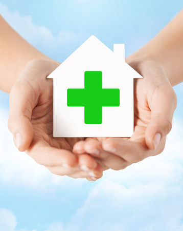eradication: care, help, charity and people concept - close up of hands holding white paper house with green cross sign over blue sky and cloud background