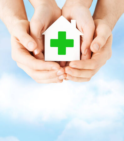 care, help, charity and people concept - close up of hands holding white paper house with green cross sign photo