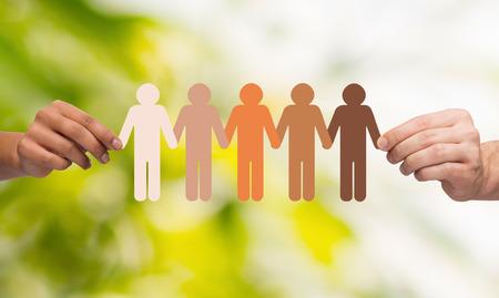 apoyo familiar: comunidad, la unidad, la gente y el apoyo concepto - par de manos que sostienen la cadena de papel personas multirraciales sobre fondo verde