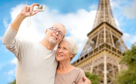 edad, turismo, viajes, tecnología y concepto de la gente - pareja senior con cámara que toma Autofoto en la calle más de la torre Eiffel de fondo