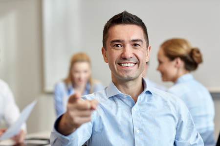 middle finger: business, people, gesture and teamwork concept - smiling businessman pointing finger to you with group of businesspeople meeting in office