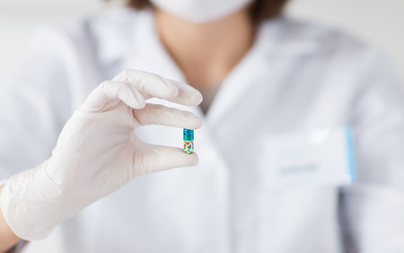 science, chemistry, biology, medicine and people concept - close up of young female scientist or doctor holding and showing pill in laboratory