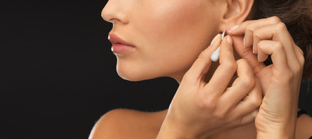 putting up: close up of beautiful woman wearing shiny diamond earrings