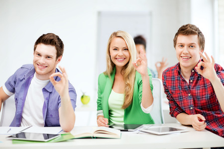 pcs: education and technology- smiling students with tablet pcs showing ok sign at school Stock Photo