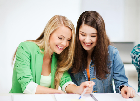 education concept - student girls pointing at notebook at school photo