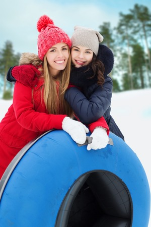 tubes: winter, leisure, sport, friendship and people concept - happy girl friends with snow tubes hugging outdoors
