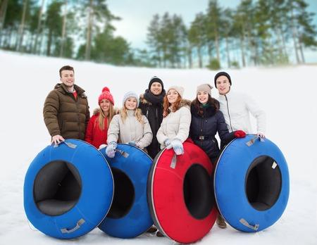 familias jovenes: invierno, el ocio, el deporte, la amistad y el concepto de la gente - grupo de amigos sonriendo con tubos de nieve al aire libre