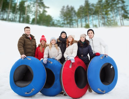 tubes: winter, leisure, sport, friendship and people concept - group of smiling friends with snow tubes outdoors
