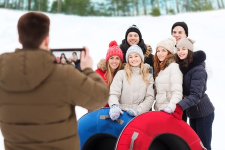 winter, leisure, sport, friendship and people concept - group of smiling friends with snow tubes taking picture by tablet pc computer outdoors photo