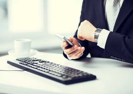 man hands with keyboard watching time and holding smartphone