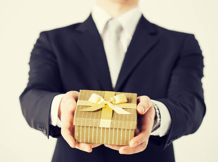 holding close: close up of man hands holding gift box. Stock Photo