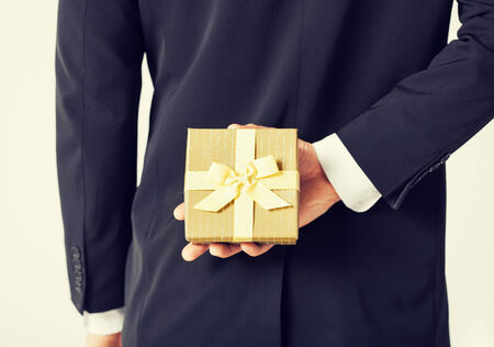 gift behind back: close up of man hands holding gift box Stock Photo