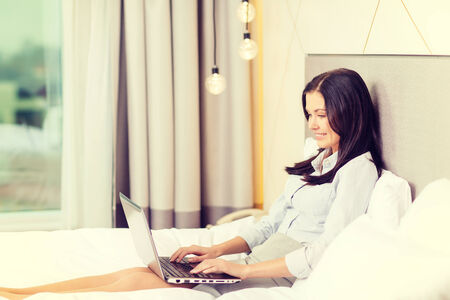 concept hotel: business, technology, internet and hotel concept - happy businesswoman with laptop computer lying in hotel in bed