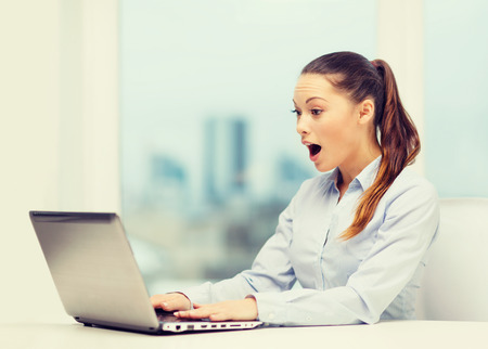 business and office concept - surprised businesswoman using her laptop computer