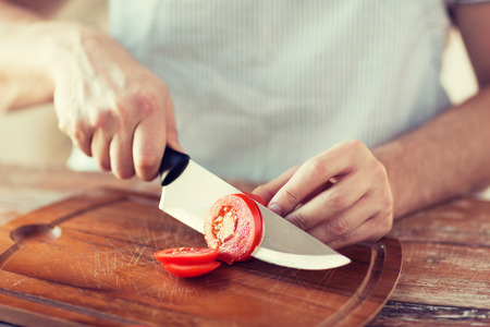 young knife: cooking and home concept - close up of male hand cutting tomato on cutting board with sharp knife