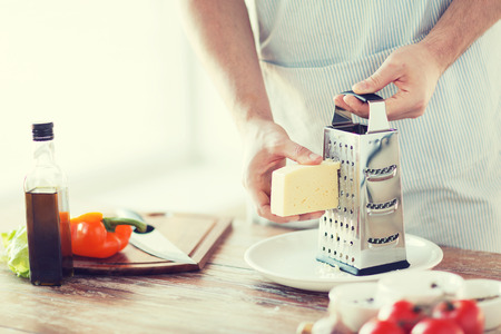 cheese grater: cooking, food and home concept - close up of male hands grating cheese Stock Photo