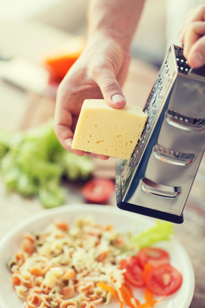 chees: cooking, food and home concept - close up of male hands grating cheese over pasta