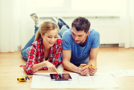trabjando en casa: reparación, construcción, renovación y casa concepto - pareja sonriente mirando la Tablet PC en el hogar Foto de archivo