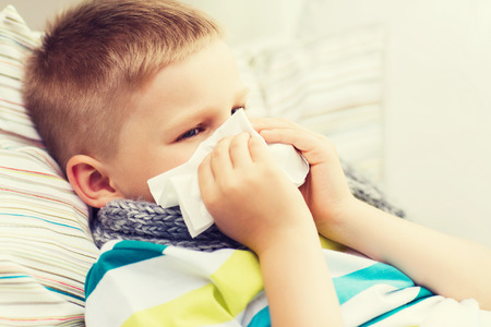 幼年期、ヘルスケアおよび医学のコンセプト - 自宅鼻を吹いているインフルエンザと病気の少年